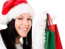 bags jul som rymmer den le kvinnan för shopping Arkivfoto