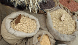 Bags of jute with oat seeds and soybeans for sale at the market. Large bags of jute with oat seeds and soybeans for sale at the market in cereals Royalty Free Stock Photo