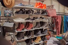 Bags, pants, shoes, sneakers and womens dress boots on shelves for sale in store of Toledo. Bags, pants, shoes, sneakers and womens dress boots on shelves for stock images