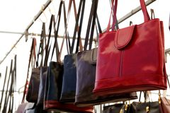 Bags rows in retail shop handbags leather red. In foreground royalty free stock photo