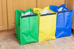 Bags for Sorting Household Waste. Green, blue and yellow bags are ready to use in sorting household waste Stock Image