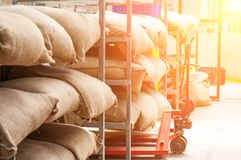 Bags in the warehouse on the racks. Coffee, arabica, rice Stock Photo