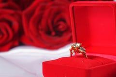 Bague à diamant d'or dans la boîte et la rose de rouge Images stock