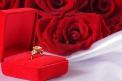Bague à diamant d'or dans la boîte et la rose de rouge Image libre de droits