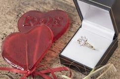 Bague à diamant et sucreries en forme de coeur sur la table en bois Photographie stock