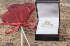 Bague à diamant et sucreries en forme de coeur sur la table en bois Images stock
