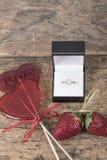 Bague à diamant et sucreries en forme de coeur sur la table en bois Photos libres de droits