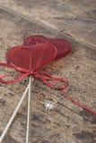 Bague à diamant et sucreries en forme de coeur sur le fond en bois Image stock