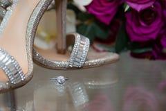 Bague à diamant placée à côté des chaussures nuptiales Photo stock