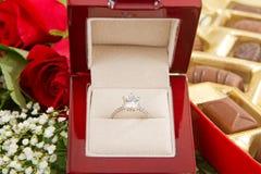 Bague de fiançailles avec des chocolats et des roses Photos stock
