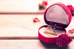 Bague de fiançailles d'or dans une boîte en forme de coeur Images libres de droits