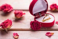 Bague de fiançailles d'or dans une boîte en forme de coeur Photo stock