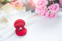 Bague de fiançailles dans la boîte rouge avec des accessoires de rose et de jeune mariée de rose Images libres de droits