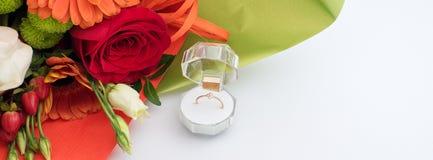 Bague de fiançailles dans un boîte-cadeau avec le bouquet lumineux des fleurs L'offre à se marier  Cadeau pour le jour du ` s de  photos stock