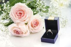 Bague de fiançailles dans une boîte et des roses roses sur le fond blanc Image stock