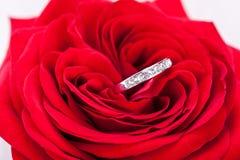 Bague de fiançailles de diamant au coeur d'une rose rouge Image libre de droits