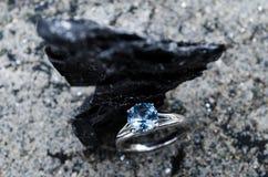 Bague de fiançailles réglée sur un morceau de charbon de bois naturel, texture noire de carbone sur des bijoux images stock