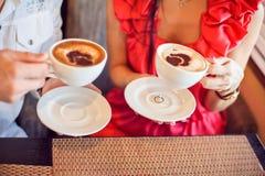 Bague de fiançailles sous une tasse de café homme et femme le tenant, avec des coeurs en café Photographie stock libre de droits