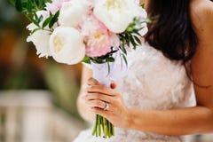 Bague de fiançailles sur la main du ` s de jeune mariée avec le bouquet Images libres de droits