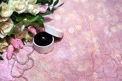 Bague de fiançailles de vue supérieure dans un boîtier blanc rond sur un fond de papier rose avec le bokeh et avec un bouquet des images stock