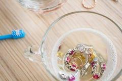 Bague ? diamant de nettoyage de bijoux avec le verre de liquide d'eau chaude et de vaisselle photographie stock libre de droits