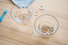 Bague ? diamant de nettoyage de bijoux avec le verre de liquide d'eau chaude et de vaisselle photo libre de droits