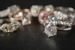 Bagues à diamant de bijoux réglées sur le fond noir image libre de droits