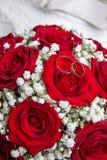 Bagues de fiançailles et bouquet nuptiale des roses rouges Photographie stock