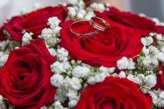 Bagues de fiançailles et bouquet nuptiale des roses rouges Image libre de droits