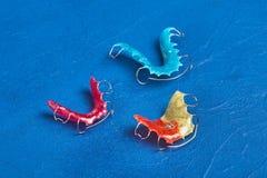 Bagues dentaires ou arrêtoirs colorés pour des dents sur le fond bleu Photographie stock libre de droits