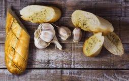 Baguette με τα βουτύρου, αρωματικές χορτάρια σκόρδου και τη φέτα του σκόρδου στο ξύλο Τοπ φωτογραφία τροφίμων άποψης στοκ εικόνες
