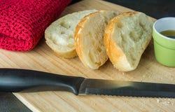 Baguette affettate sul tagliere con il panno ed il coltello dell'olio Fotografia Stock