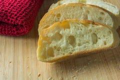 Baguette affettate sul tagliere con la fine del panno su Immagine Stock