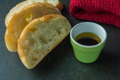 Baguette affettate sulla superficie del nero con il panno e l'olio Immagini Stock Libere da Diritti