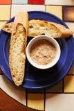 Baguette arrostite con il patè del pesce Aperitivo in un piatto blu, tavola piastrellata variopinta fotografia stock
