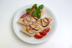 Baguette as snack with onion and tomato Stock Image