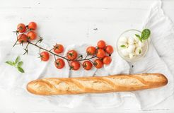 Baguette with banch of cherry-tomatoes, basil and mozzarella cheese. Baguette with banch of cherry-tomatoes, basil and bowl of mozzarella cheese on rustic white Stock Image