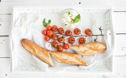 Baguette with branch of cherry-tomatoes, basil and. Mozzarella cheese on rustic white wooden tray, top view Stock Photos