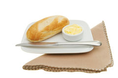 Baguette bread roll, butter and knife on a plate. Baguette bread roll with butter and a knife on a plate with a napkin Stock Photos