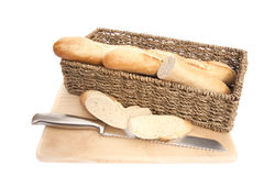 Baguette bread in rustic basket on chopping board Royalty Free Stock Image