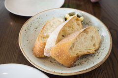 Baguette bread with small butter bow. On wooden table Stock Photo