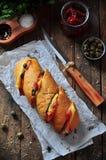 Baguette cocido relleno con tocino, queso, tomates secados al sol y alcaparras Foto de archivo