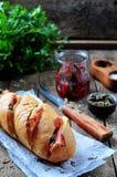 Baguette cocido relleno con tocino, queso, tomates secados al sol y alcaparras Foto de archivo libre de regalías