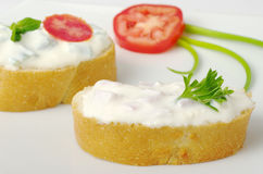 Baguette with Cream Cheese Spread. Baguette bread with cream cheese spread decorated with tomato, parsley and green onion on white plate (selective focus Royalty Free Stock Photography