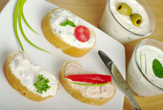 Baguette with Cream Cheese Spread. Baguette bread with cream cheese spread decorated with tomato, red pepper, parsley and green onion on white plate (Selective Stock Photography