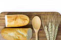 Baguette, cucchiaio e grano francesi sul bordo di legno Fotografia Stock Libera da Diritti