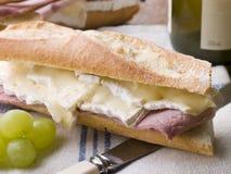 Baguette de brie et de jambon avec du vin blanc et des raisins Images stock