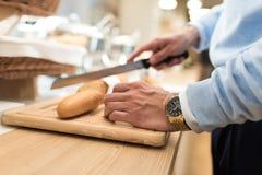 Baguette de Cut d'homme d'affaires pour son petit déjeuner images stock