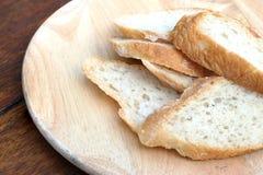 Baguette de pain blanc coupé en tranches et de pain français sur le conseil en bois Photo libre de droits