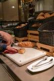 Baguette del corte de la mano de la muchacha con un cuchillo fotografía de archivo